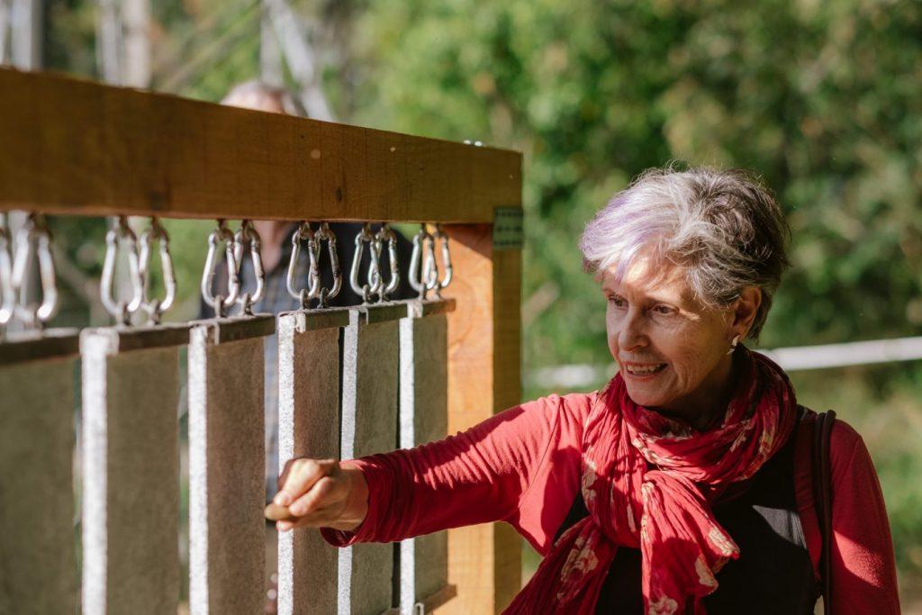 """Cristina Ataíde interagindo com a obra """"Lithos"""" (Kaitlin Ferguson & Natalia Bezerra, 2019).[Créditos da Imagem: Luís Belo p/ POLDRA - Public Sculpture Project Viseu. 2019-10-12.][Cedência: POLDRA - Public Sculpture Project Viseu. 2019-11-13]"""